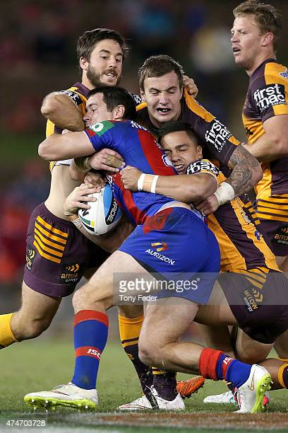 James McManus of the Knights is tackled by the Broncos defence during the round 11 NRL match between the Newcastle Knights and the Brisbane Broncos...