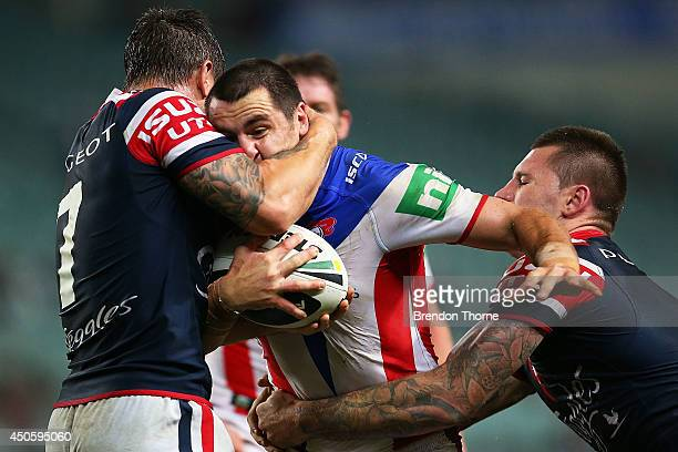 James McManus of the Knights is tackled by the Roosters defence during the round 14 NRL match between the Sydney Roosters and the Newcastle Knights...