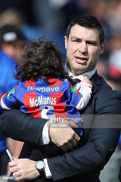 James McManus of the Knights with daughter Emelyn say farewell to supporters after retiring from football the round 23 NRL match between the...