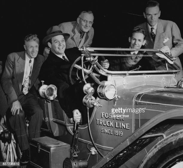James Melton famed tenor and radio star and avid antique automobile fan grasps the hand broke of an old model as several members of the Horseless...