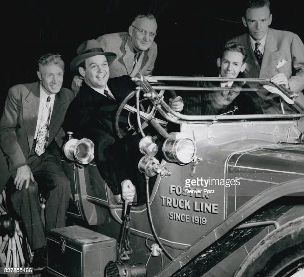 James Melton famed tenor and radio star and avid antique automobile fan grasps the handbrake of an old model as several members of the Horseless...