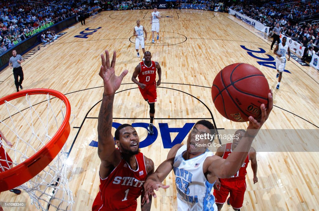 James Michael McAdoo of the North Carolina Tar Heels drives against Richard Howell of the North Carolina State Wolfpack during the semifinals of the...