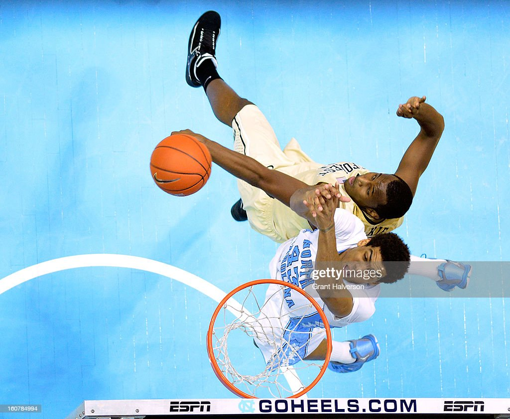James Michael McAdoo of the North Carolina Tar Heels drives to the basket against Travis McKie of the Wake Forest Demon Deacons during play at the...