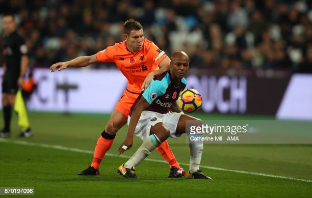 James Milner of Liverpool and Andre Ayew of West Ham United during the Premier League match between West Ham United and Liverpool at London Stadium...