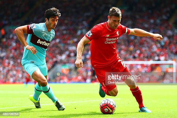 James Milner of Liverpool and James Tomkins of West Ham United compete for the ball during the Barclays Premier League match between Liverpool and...