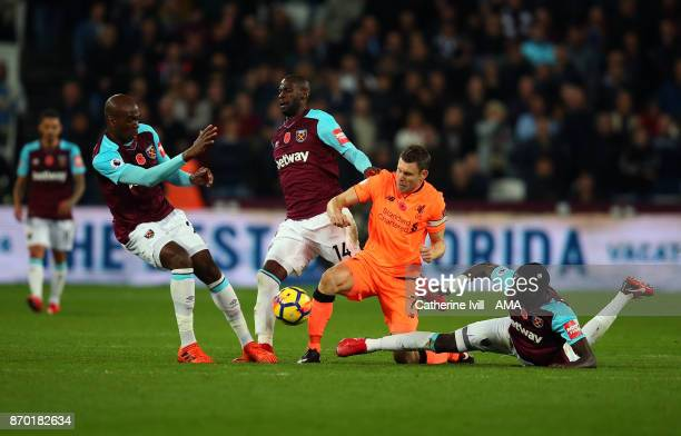 James Milner of Liverpool battles with Angelo Ogbonna Pedro Obiang and Cheikhou Kouyate of West Ham United during the Premier League match between...