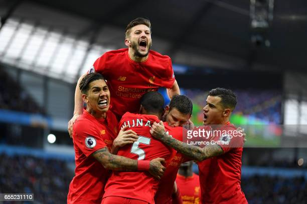 James Milner of Liverpool celebrates scoring his sides first goal with his Liverpool team mates during the Premier League match between Manchester...