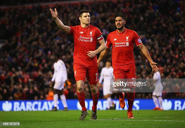 James Milner of Liverpool celebrates with Emre Can as he scores their first goal from a penalty during the Barclays Premier League match between...