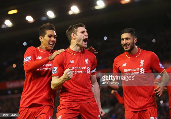 James Milner of Liverpool celebrates with Roberto Firmino and Emre Can as he scores their first goal from a penalty during the Barclays Premier...