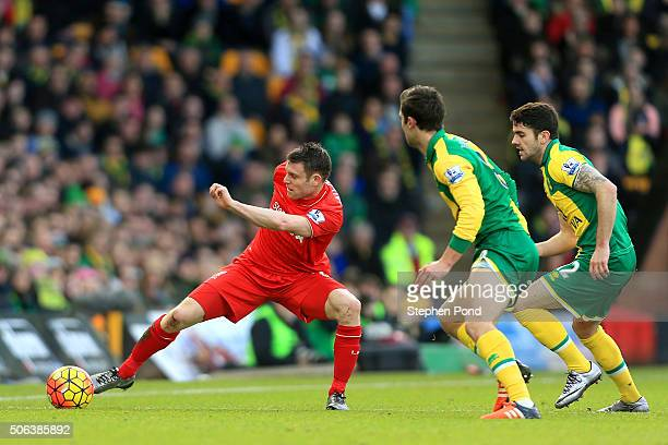 James Milner of Liverpool controls the ball under pressure of Robbie Brady and Ivo Pinto of Norwich City during the Barclays Premier League match...