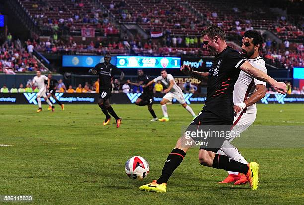 James Milner of Liverpool FC handles the ball as Mohamed Salah of AS Roma defends during a friendly match at Busch Stadium on August 1 2016 in St...