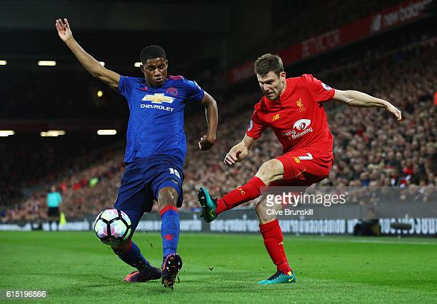 James Milner of Liverpool is challenged by Marcus Rashford of Manchester United during the Premier League match between Liverpool and Manchester...
