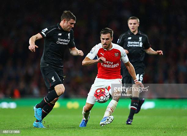 James Milner of Liverpool is closed down by Aaron Ramsey of Arsenal during the Barclays Premier League match between Arsenal and Liverpool at...