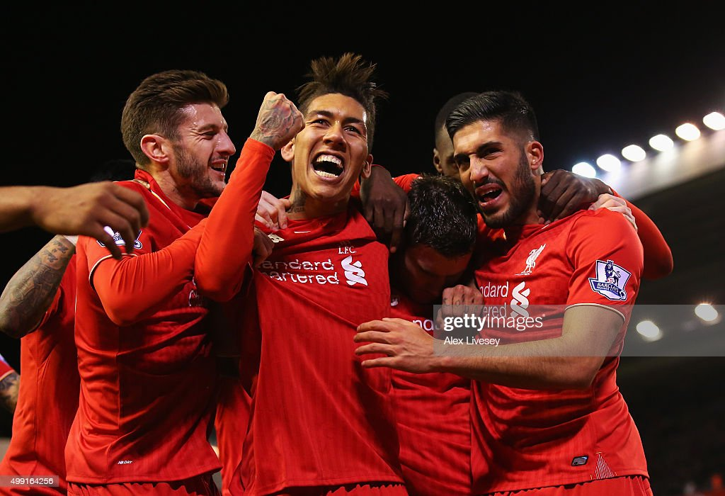 James Milner of Liverpool is congratulated by Adam Lallana Roberto Firmino Emre Can as he scores their first goal from a penalty during the Barclays...