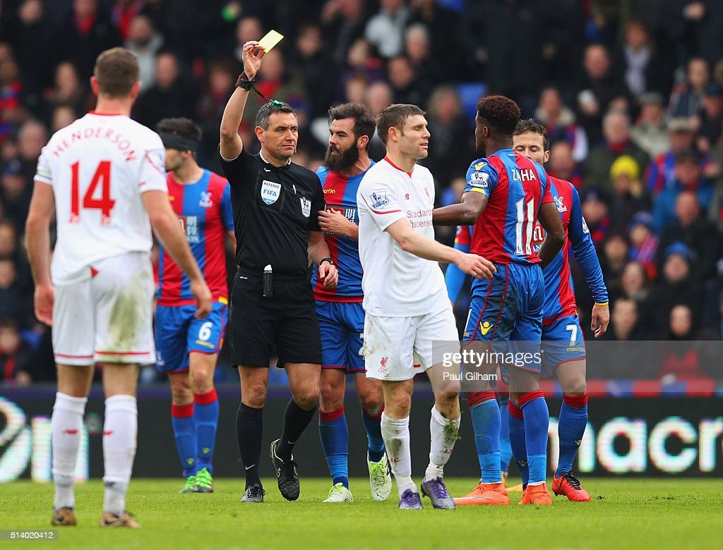 James Milner of Liverpool is shown a second yellow card by referee Andre Marriner and is sent off during the Barclays Premier League match between...