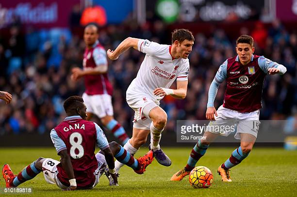 James Milner of Liverpool runs with the ball past Idrissa Gana and Ashley Westwood of Aston Villa during the Barclays Premier League match between...