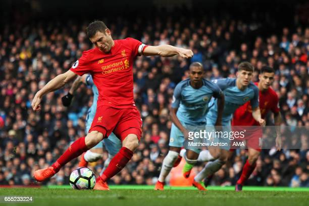 James Milner of Liverpool scores a penalty to make the score 01 during the Premier League match between Manchester City and Liverpool at Etihad...