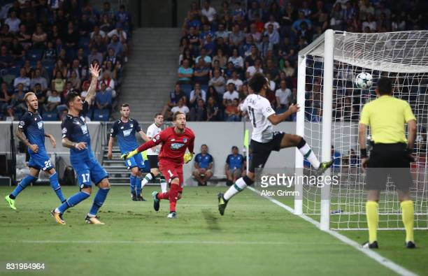 James Milner of Liverpool scores while Oliver Baumann of Hoffenheim looks on during the UEFA Champions League Qualifying PlayOffs Round First Leg...