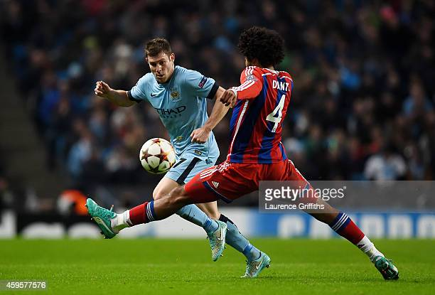 James Milner of Manchester City and Dante of Bayern Muenchen compete for the ball during the UEFA Champions League Group E match between Manchester...