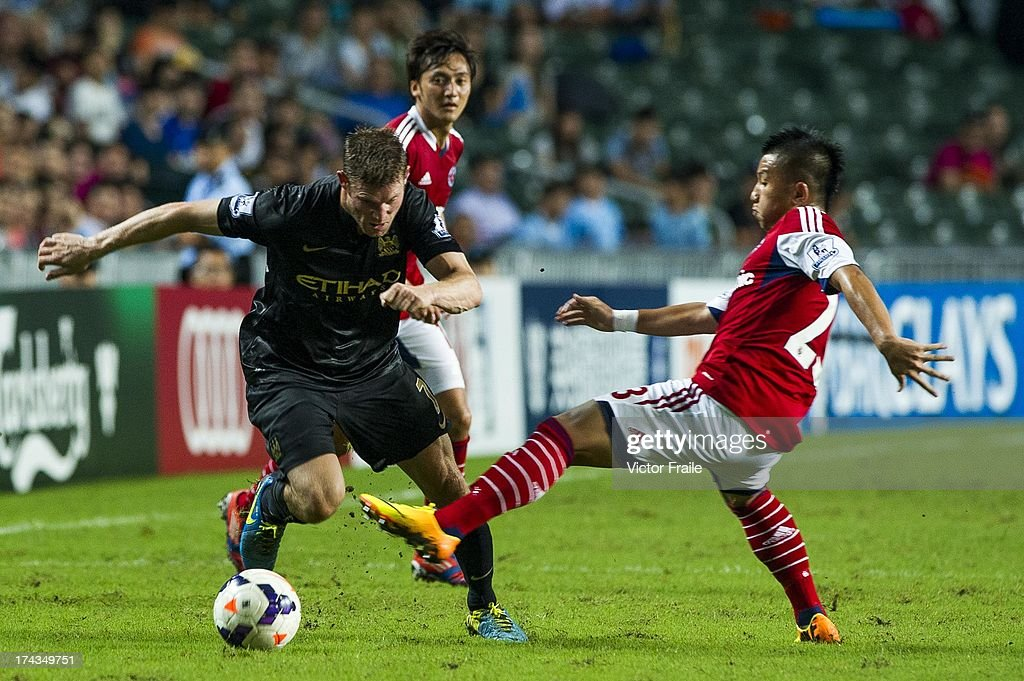 James Milner of Manchester City and Luk Michael Chi Ho of South China during the Barclays Asia Trophy Semi Final match between Manchester City and...