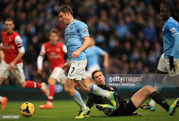 James Milner of Manchester City is brought down for a penalty by Wojciech Szczesny of Arsenal during the Barclays Premier League match between...