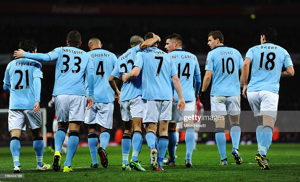<a gi-track='captionPersonalityLinkClicked' href=/galleries/search?phrase=James+Milner&family=editorial&specificpeople=214576 ng-click='$event.stopPropagation()'>James Milner</a> of Manchester City (7) is congratulated by team mates as he scores their first goal during the Barclays Premier League match between Arsenal and Manchester City at Emirates Stadium on January 13, 2013 in London, England.