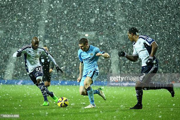 James Milner of Manchester City takes on Youssuf Mulumbu and Andre Wisdom of West Brom as the snow falls during the Barclays Premier League match...