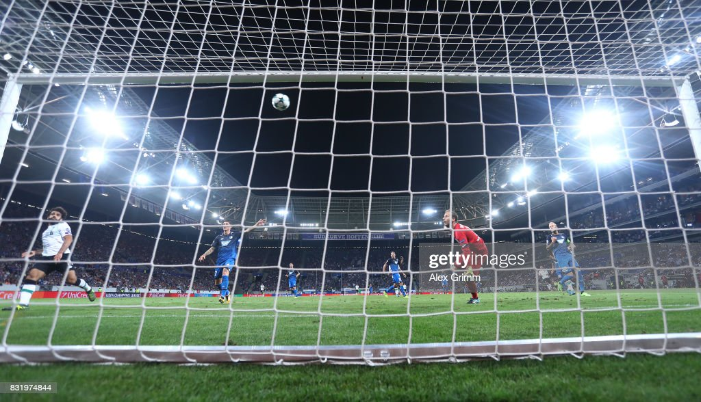 James Milner (not pictured) scores while Oliver Baumann of Hoffenheim (red) looks on during the UEFA Champions League Qualifying Play-Offs Round First Leg match between 1899 Hoffenheim and Liverpool FC at Wirsol Rhein-Neckar-Arena on August 15, 2017 in Sinsheim, Germany.