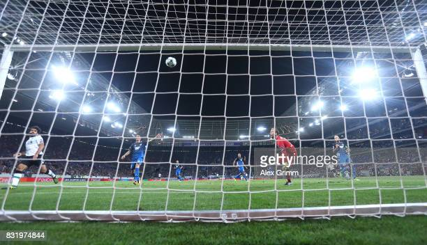 James Milner scores while Oliver Baumann of Hoffenheim looks on during the UEFA Champions League Qualifying PlayOffs Round First Leg match between...