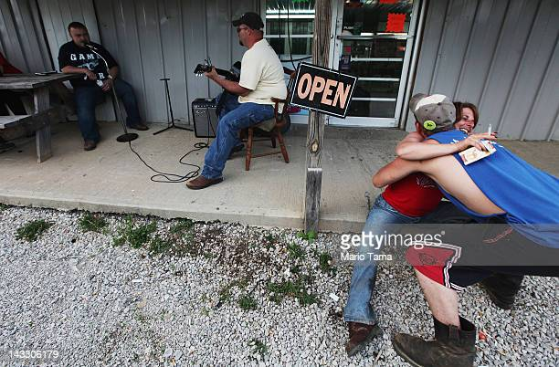 James Moore plays the guitar as Robert Go sings while revelers hug at Joe's Meat Market in Owsley County on April 20 2012 in Booneville Kentucky...