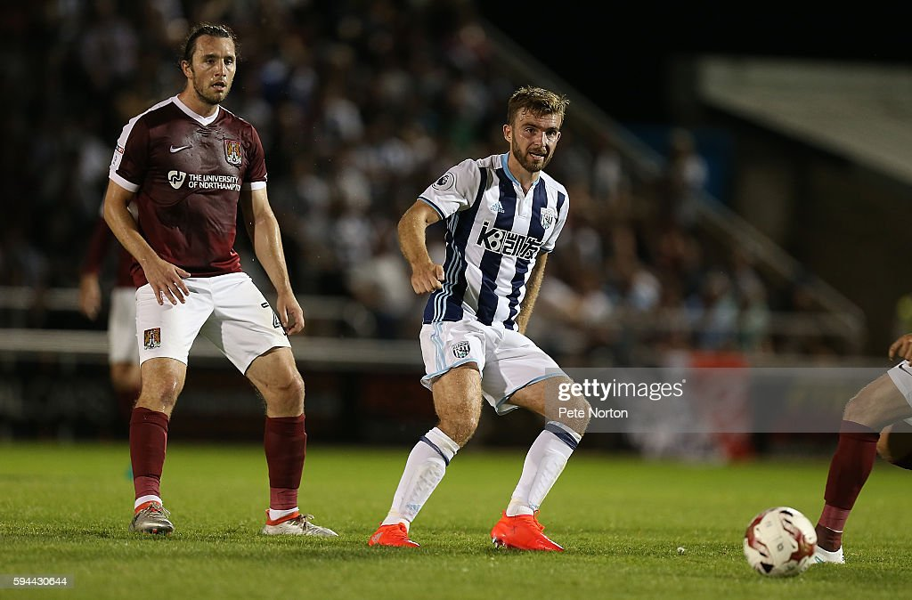 James Morrison of West Bromwich Albion plays the ball watched by JohnJoe O'Toole of Northampton Town during the EFL Cup second round match between...