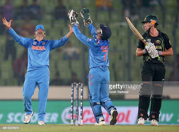 James Muirhead of Australia looks on as MS Dhoni of India celebrates catching him out to win the match during the ICC World Twenty20 Bangladesh 2014...