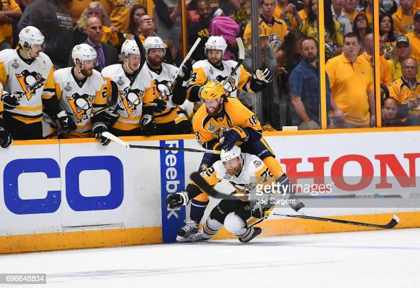James Neal of the Nashville Predators checks Patric Hornqvist of the Pittsburgh Penguins near the Penguins bench area during the second period of...