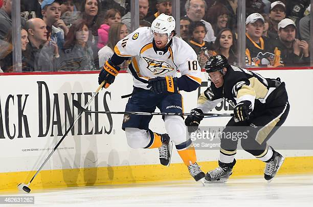 James Neal of the Nashville Predators moves the puck up ice in front of Patric Hornqvist of the Pittsburgh Penguins at Consol Energy Center on...