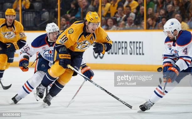 James Neal of the Nashville Predators skates against Iiro Pakarinen and Kris Russell of the Edmonton Oilers during an NHL game at Bridgestone Arena...
