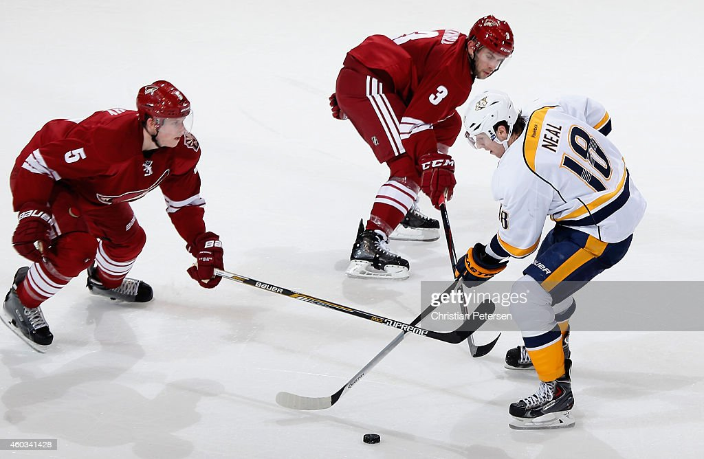 James Neal #18 of the Nashville Predators skates with the puck under pressure from Connor Murphy #5 and Keith Yandle #3 of the Arizona Coyotes during the third period of the NHL game at Gila River Arena on December 11, 2014 in Glendale, Arizona. The Predators defeated the Coyotes 5-1.