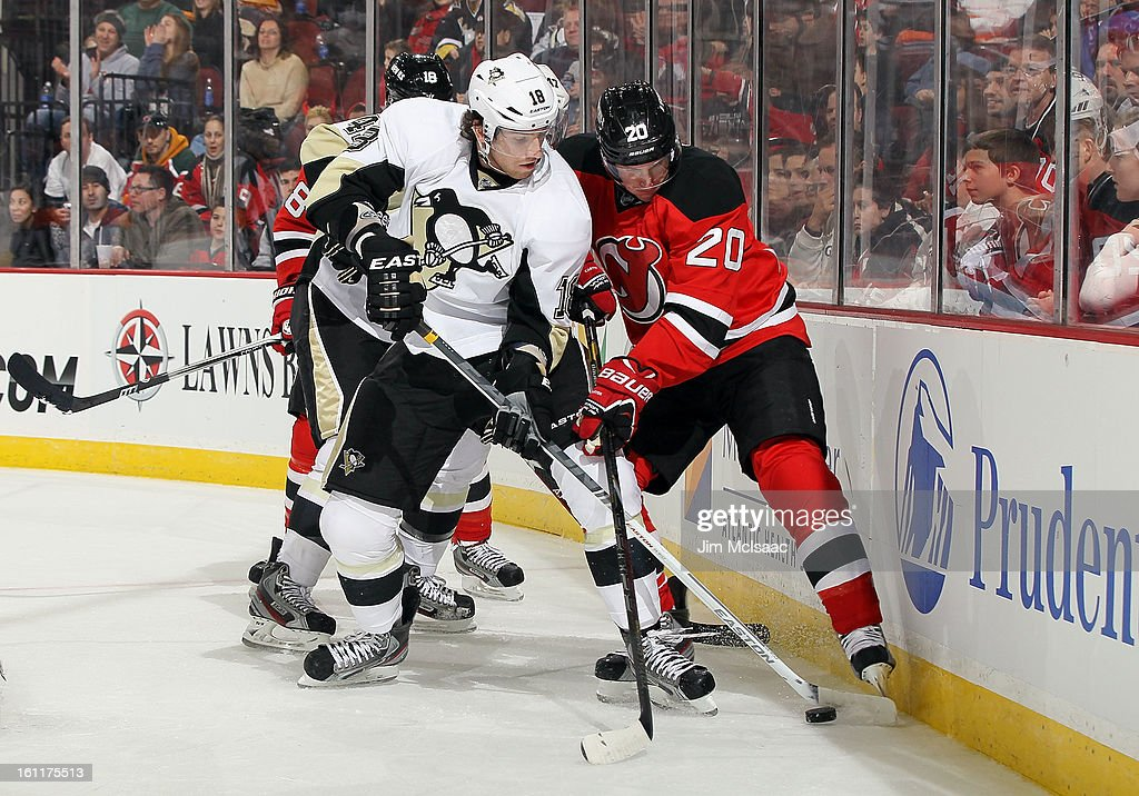 James Neal #18 of the Pittsburgh Penguins battles for the puck against Ryan Carter #20 of the New Jersey Devils at the Prudential Center on February 9, 2013 in Newark, New Jersey.