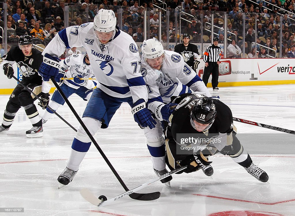 James Neal #18 of the Pittsburgh Penguins gets knocked down by Steven Stamkos #91 while battling for the puck against Victor Hedman #77 of the Tampa Bay Lightning on March 4, 2013 at Consol Energy Center in Pittsburgh, Pennsylvania. Pittsburgh won the game 4-3