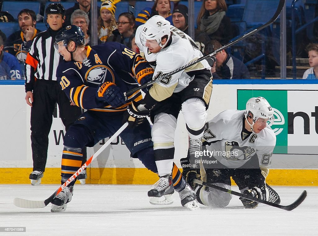 James Neal #18 of the Pittsburgh Penguins jumps over teammate Sidney Crosby #87 while defended by Henrik Tallinder #20 of the Buffalo Sabres on February 5, 2014 at the First Niagara Center in Buffalo, New York.