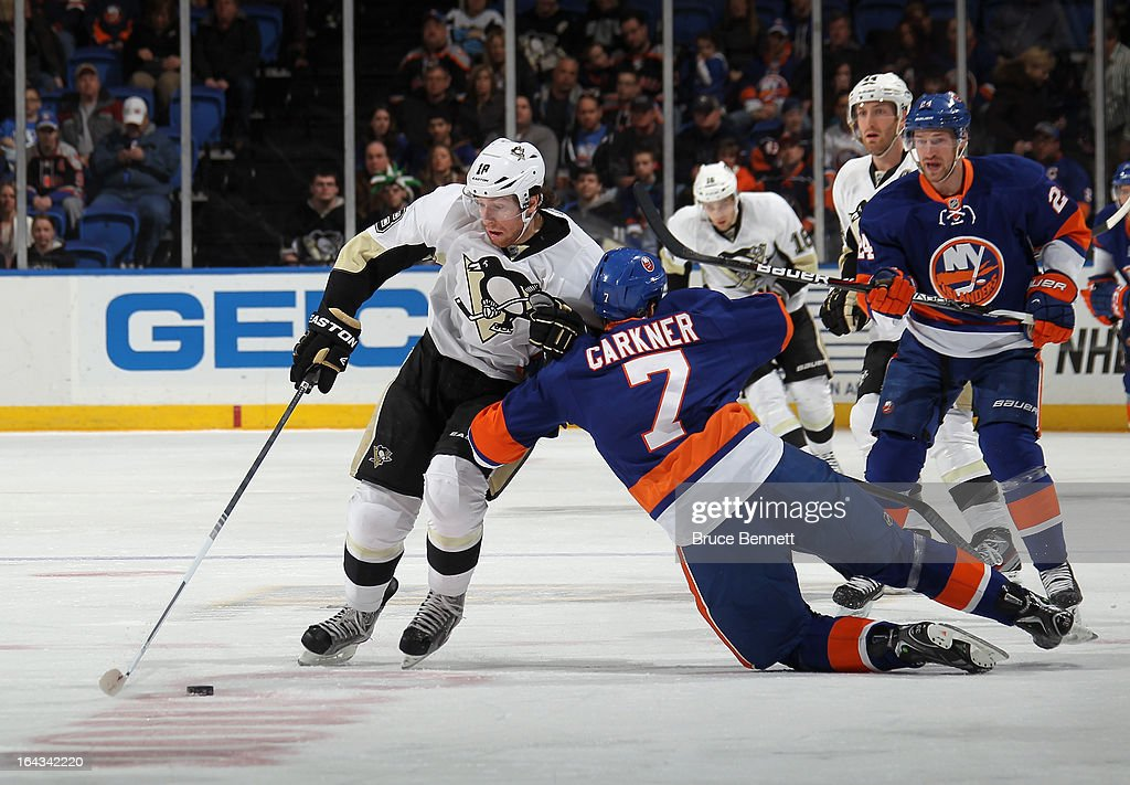James Neal #18 of the Pittsburgh Penguins moves around Matt Carkner #7 of the New York Islanders at Nassau Veterans Memorial Coliseum on March 22, 2013 in Uniondale, New York.