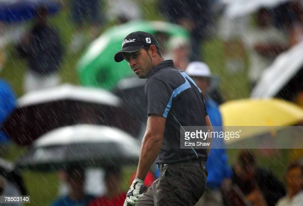James Nitties of Australia gets caught in heavy rain on the 18th hole during round four of the Australian Open Championship at The Australian Golf...