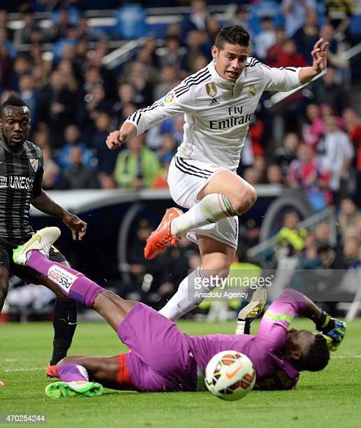 James of Real Madrid is in action against Kameni during the La Liga match between Real Madrid and Malaga at Estadio Santiago Bernabeu in Madrid Spain...