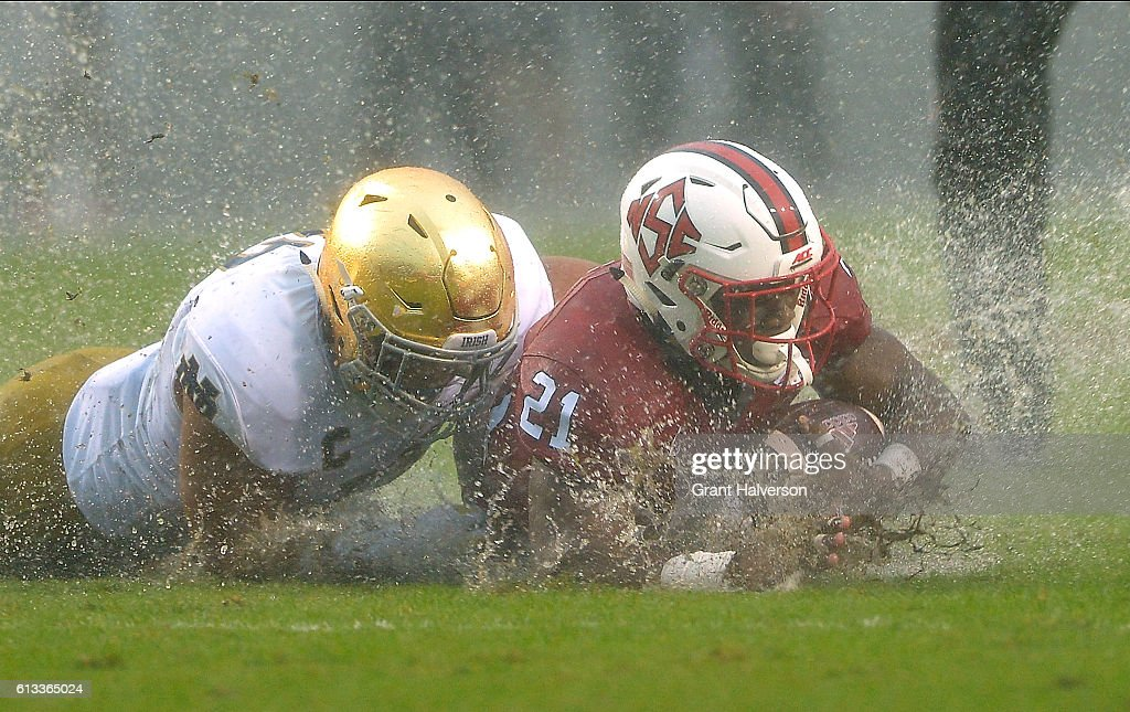 James Onwualu of the Notre Dame Fighting Irish tackles Matthew Dayes of the North Carolina State Wolfpack during the game at Carter Finley Stadium on...