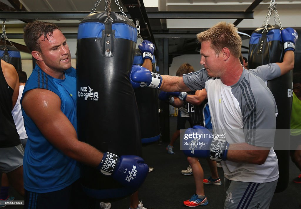 James Parsons (L) holds the bag for Tom McCartney during a Blues training session with Shane Cameron at Shane Cameron Fitness on January 23, 2013 in Auckland, New Zealand.