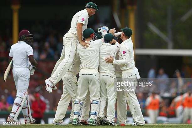 James Pattinson of Australia jumps to join his team mate congratulate Joe Burns of Australia as he celebrates taking the catch to dismiss Jason...