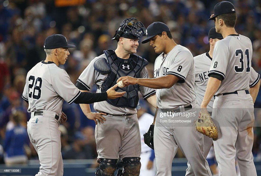 James Pazos #67 of the New York Yankees gives up the ball to manager Joe Girardi #28 as he is relieved in the sixth inning while Brian McCann #34 looks on during MLB game action against the Toronto Blue Jays on September 23, 2015 at Rogers Centre in Toronto, Ontario, Canada.