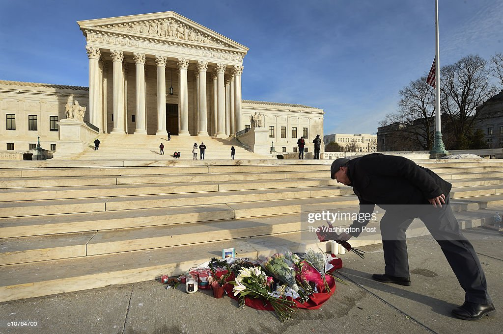 James Peck of Springfield VA lays flowers down at a makeshift memorial for Supreme Court Justice Antonin Scalia outside the Supreme Court of the...