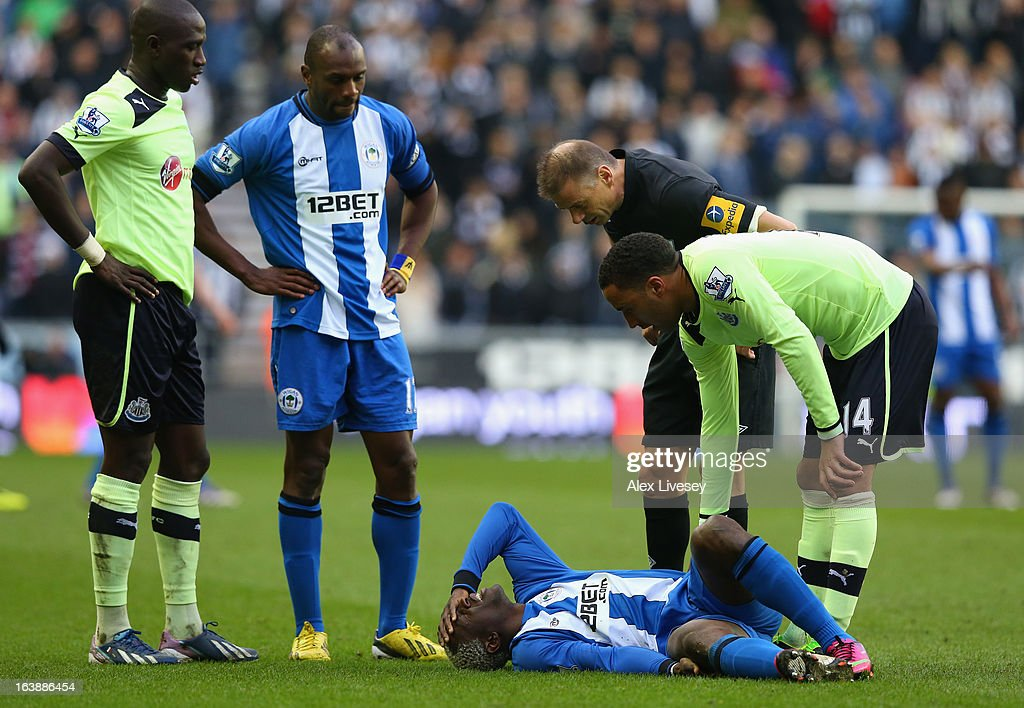 James Perch of Newcastle United checks on Arouna Kone of Wigan Athletic following a strong challenge during the Barclays Premier League match between Wigan Athletic and Newcastle United at the DW Stadium on March 17, 2013 in Wigan, England.
