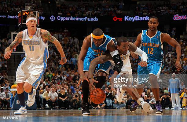 James Posey of the New Orleans Hornets and JR Smith of the Denver Nuggets battle for a loose ball as Chris Andersen of the Nuggets and Hilton...