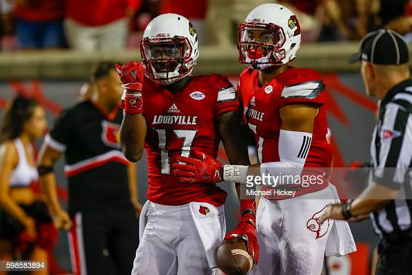James Quick of the Louisville Cardinals signals a completed catch that would eventually result in a touchdown as Reggie Bonnafon of the Louisville...
